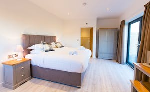 The Granary - Bedroom 1 is fresh, light and airy, with French doors that open out onto a patio