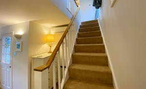 Stairs leading to landing and bedrooms and upper door