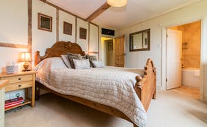 Ensuite bedroom with carved wooden Kingsize bed and beamed walls