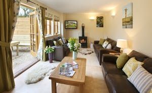 The sitting room has comfy leather sofas and seats all the family well and has french windows opening onto the sunny patio