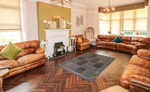 Peak Manor - Warm wood flooring and fat leather sofas in the lounge
