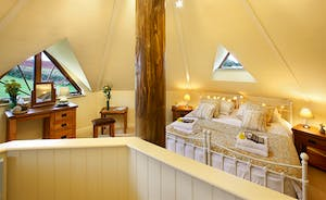 The triangular windows of the romantic master bedroom have stunning views