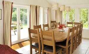 Large oak dining table seating 14 comfortably on solid oak chairs.