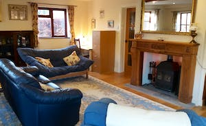 Large lounge area with woodburner. Seating includes a double futon