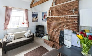 The striking red brick fireplace is a lovely focal feature