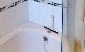 Family bathroom with P shaped bath, power shower over, toilet and basin. Marble floor.