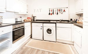 The kitchen is equipped with a dishwasher, washer/dryer, oven, hobs, microwave and fridge/freezer