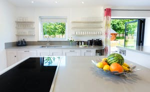 Fuzzy Orchard - A bright and airy kitchen with doors that open onto the patio