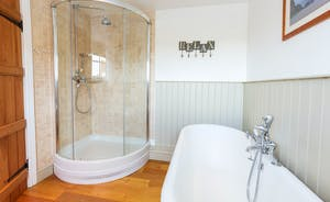 Frog Street - The Orchard Suite bathroom has a roll top bath and a shower cubicle