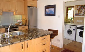 ... leading to utility room with washing machine and tumble dryer.