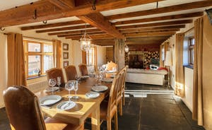 The sitting room/dining room is packed with character; old beams and a wood-burning stove