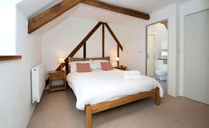 Pipits Retreat, Stonehayes Farm: Bedroom 1 has an en suite shower room; rustic beams and exposed wall timbers add to the country character