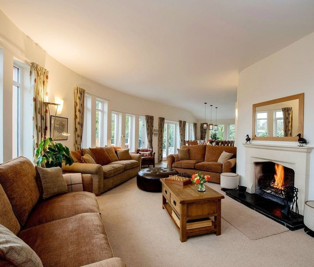 Comfortable curved sitting room with roaring open fire