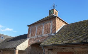 A Victorian clock tower, herringbone brickwork; once part of an historic estate, this was the stabling and gamekeeper's cottage