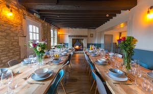 The Plough - The dining room: exposed stone walls, big chunky beams, and a wood-burner to one end