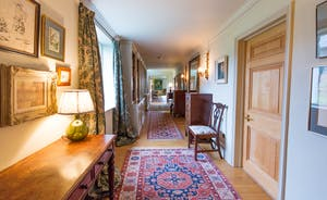 House On The Hill - A corridor packed with books and art leads to the sitting room and drawing room