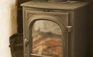 The reception room boasts a cosy log burner