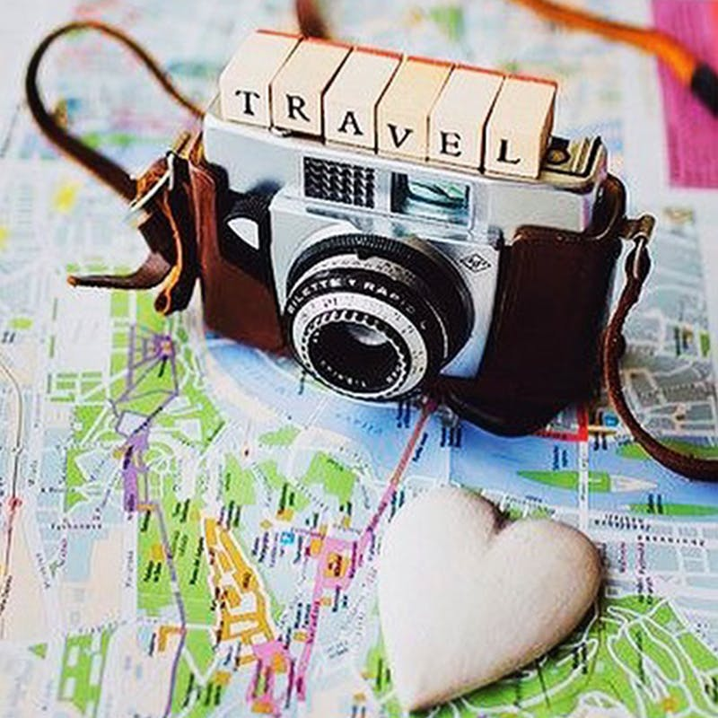 vintage camera on a map with scrabble letters saying travel