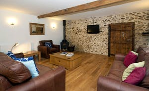 Wagtail Corner, Stonehayes Farm: Cosy sofas and a wood-burning stove to one end of the living space